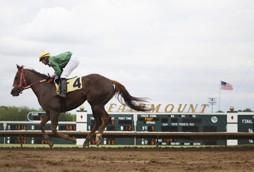 A jockey rides a horse back past the finish line after a race on opening day at Fairmount Park.