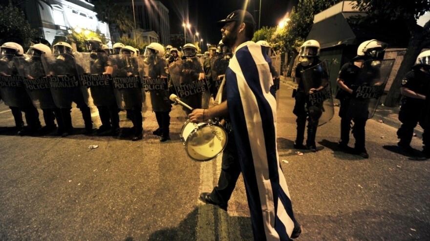 A demonstrator plays drum in front of riot police outside the Greek Parliament in Athens. The protesters aren't the usual leftists and trade unionists with red banners. They're mostly middle-class Greeks waving the white and blue national flag.