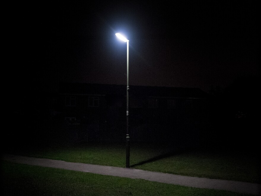A streetlight illuminates a rural footpath.
