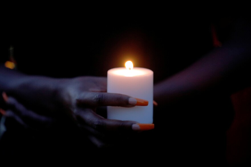 "A woman holds a candle at a ""Justice for Breonna"" vigil in Boston."