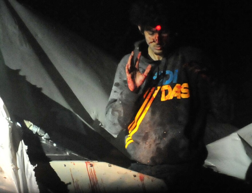 Boston bombings suspect Dzhokhar Tsarnaev on April 19 as he emerged from a boat stored in a Watertown, Mass., backyard. The red dot of a police sharpshooter's laser sight can be seen on his forehead.