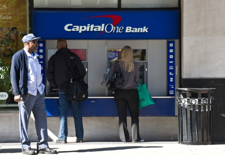 People use an ATM at a Capital One Bank branch in Washington in April 2012.