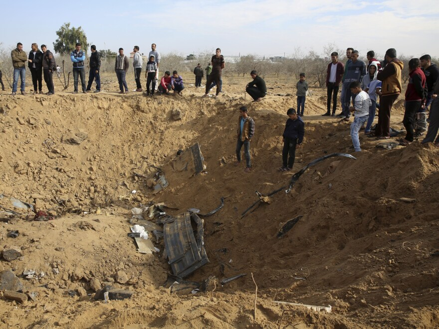 Palestinians inspect a crater made Monday by an Israeli strike east of Khan Younis, in the Gaza Strip.