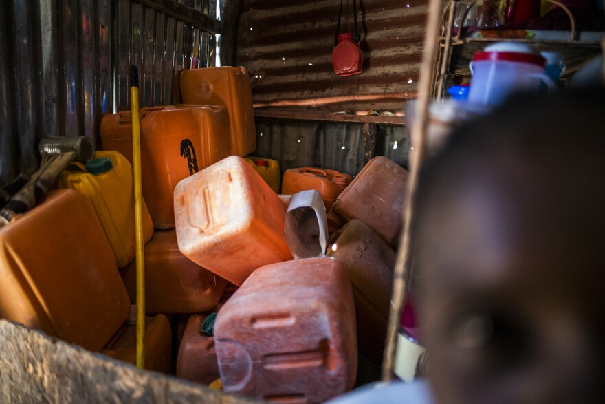 Empty jugs for water sit in a corner of Berthenid Dasny's home. Outside her door sits a large pile of stone and sand that she has been gradually purchasing in hopes of someday building a new home.