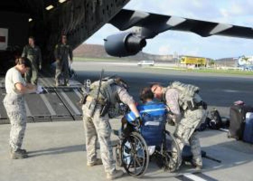 Military personnel in St. Croix prepare to load a patient for an evacuation flight to a hospital on the U.S. mainland.