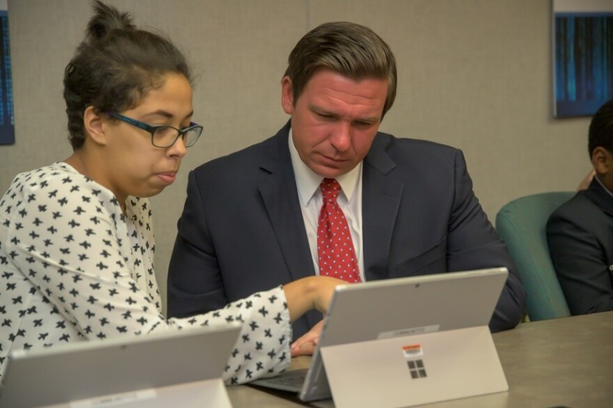 16-year-old Emily Perez is a sophomore at Lincoln High School in Tallahassee. She shows Governor Ron DeSantis her work during Coding Day at the capitol.