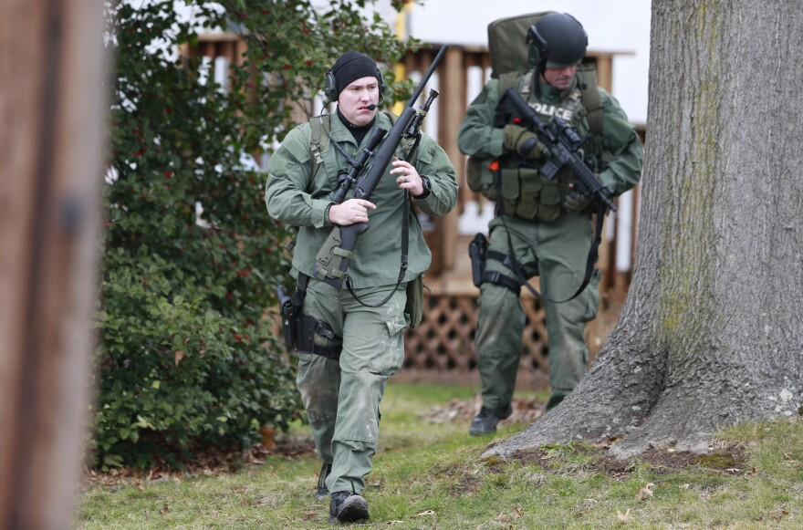 Police move near a home in Souderton, Pa., Monday, as they search for a suspect in the shooting deaths of six people.
