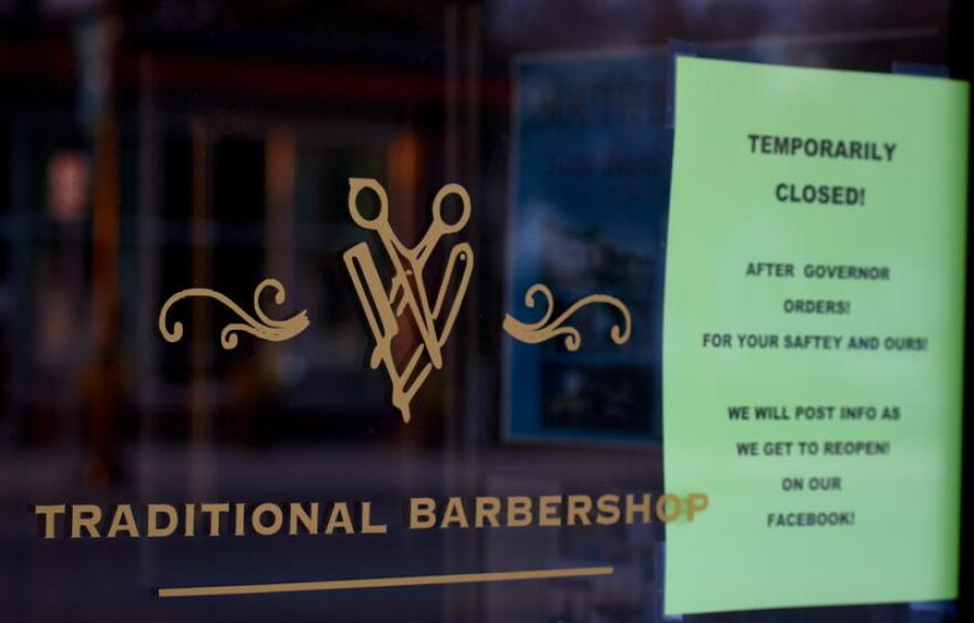"Photo caption: Boulanger's Barberie in South Bend displays a sign citing it's closure due to Gov. Eric Holcomb's ""Stay-At-Home"" order."