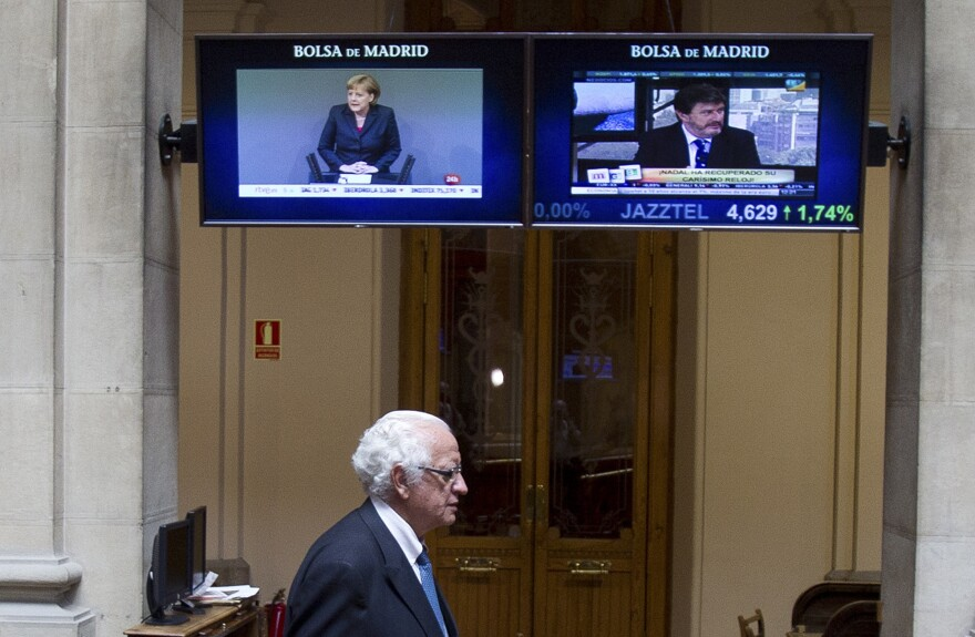 German Chancellor Angela Merkel is seen on a screen as a broker arrives at the stock exchange in Madrid on Thursday.