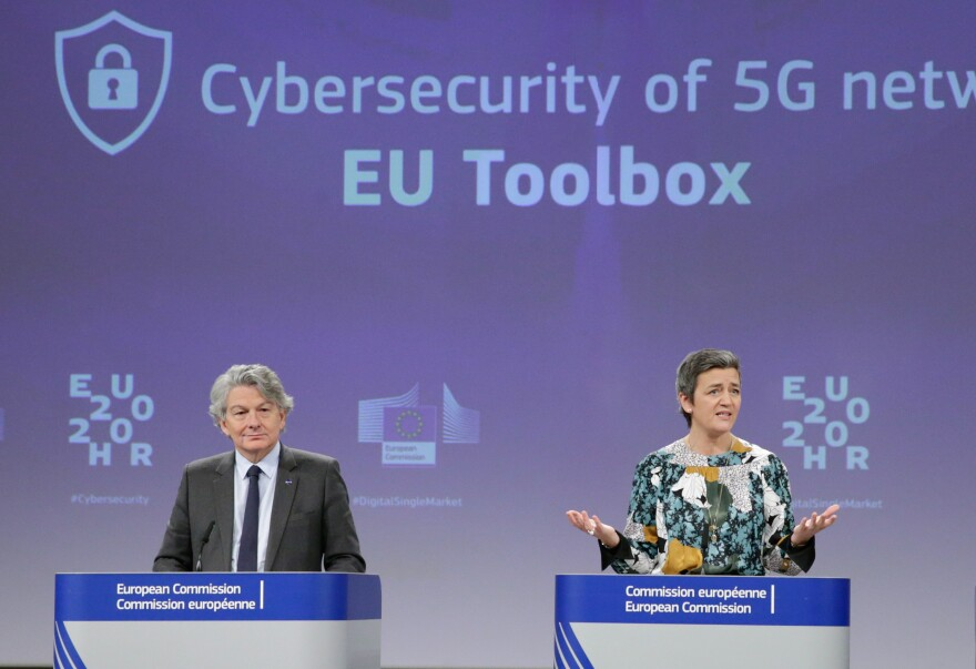 Two European Commission officials, Thierry Breton (left) and Margrethe Vestager (right), give a press conference on 5G security Wednesday in Brussels. The EU recommended that member states screen telecom firms, but did not call for banning any by name. The Chinese telecom Huawei said it welcomed the decision and hopes to take part in building 5G networks in Europe.