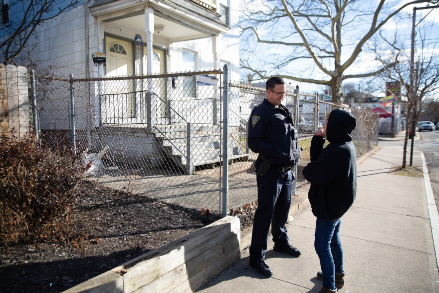 Officer Christian Bruckhart checks in with a resident of New Haven's Fair Haven neighborhood. Community building is a priority for many younger officers.