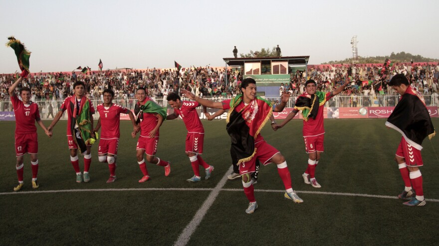 Afghanistan's soccer players dance to celebrate beating Pakistan, in a friendly match played Tuesday in Kabul.