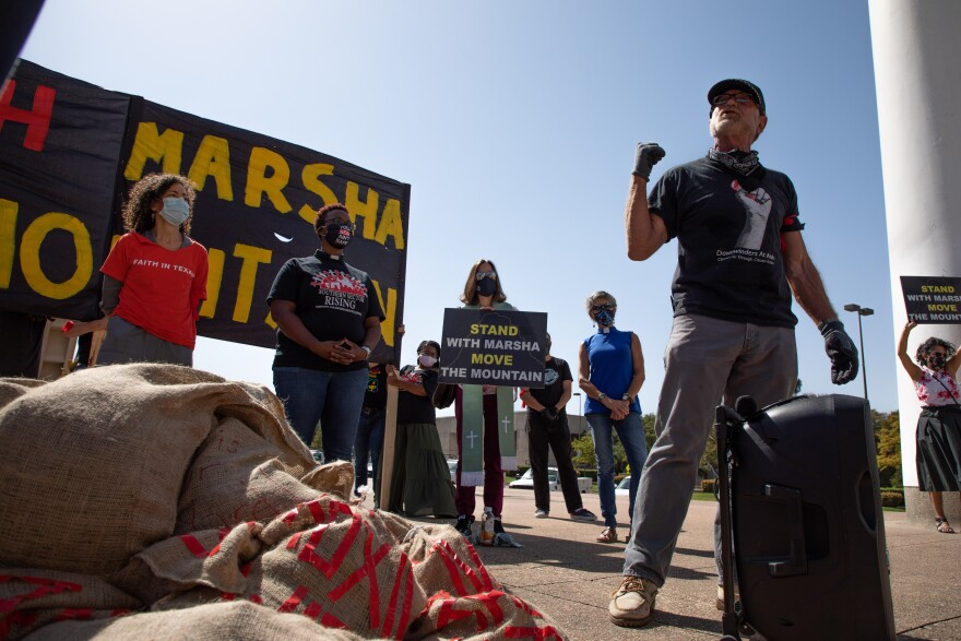 Jim Schermbeck is the director of the environmental group Downwinders at Risk. He wears a black shirt and has his fist up as he speaks at Monday's Action to relocate Shingle Mountain. There's a huge pile of of brown sack bags next to him.