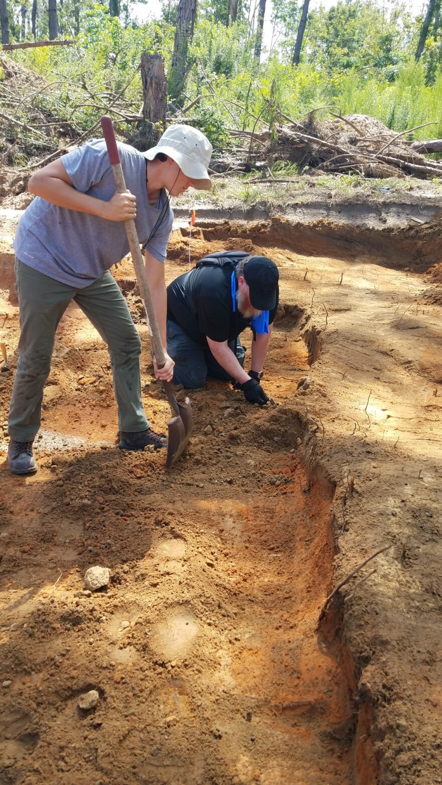 USF Masters student Chris Turner, kneeling, and forensic anthropology high school intern Sean Boland, standing, work on the site of the Dozier School for Boys in Marianna in June.
