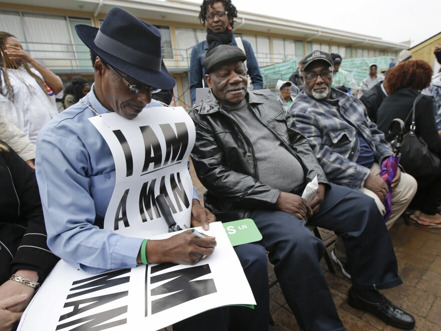 Cleophus Smith (left), autographs a poster at the National Civil Rights Museum on Thursday, April 4, 2013, in Memphis, Tenn. The poster is a reproduction of the signs he and Alvin Turner (center) and Baxter Leach (right), carried when they were part of the 1968 sanitation workers strike in Memphis.