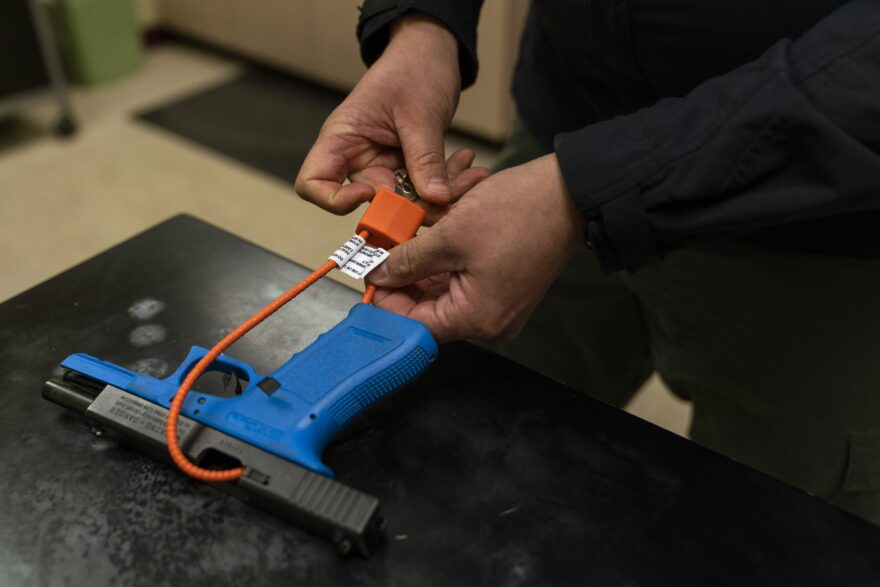 Sgt. Brandon White of the Multnomah County Sheriff's Office puts a cable lock on a training Glock on January 14, 2019 in Portland, Oregon. The Sheriff's office gives out gun locks for free to anyone who wants one.