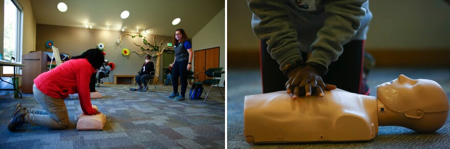 (Left) Joy Eloi, 14, and Jan Garduno (right) practice compressions on a CPR training mannequin during the first-aid class for hikers.