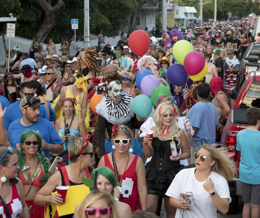 A big crowd walks down a Key West street during the Fantasy Fest masquerade march in 2018.