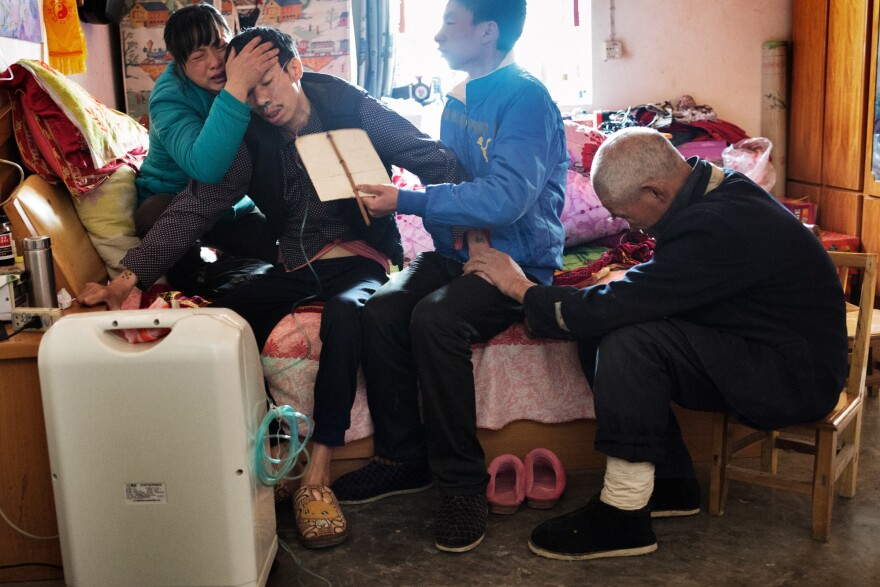 Collapsing a second time in the same day, shortly after trying to urinate on a commode, He Quangui struggles to breathe. His son He Jingbo fans him with a piece of cardboard while his wife Mi Shixiu and father He Decheng hold him, crying. The next morning, he would try to kill himself.