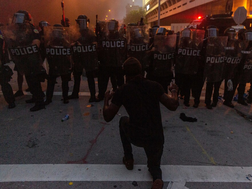 A protestor kneels and raises his hand in front of a line of riot police during a protest against police brutality in Miami on May 30, in response to the recent death of George Floyd, an unarmed black man who was killed by police.