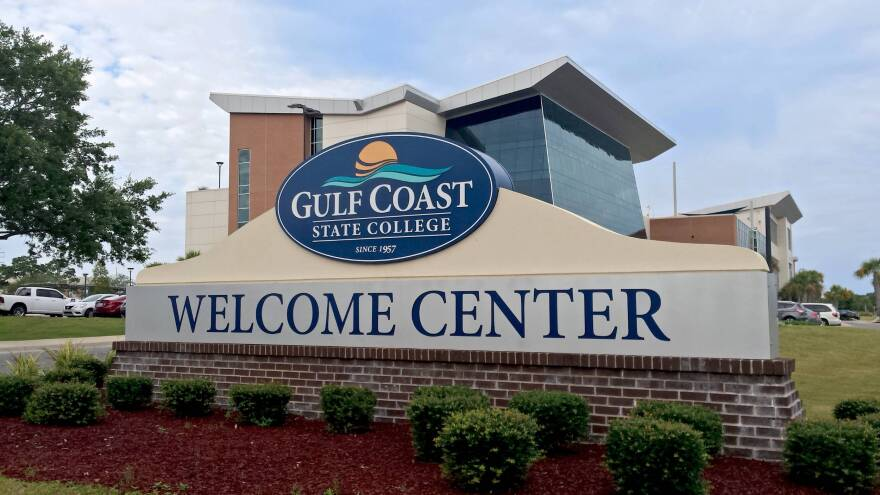Welcome sign for Gulf Coast state college surrounded by green, round bushes