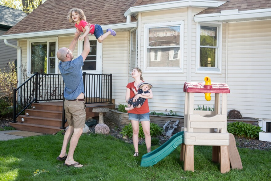 Karli-Rae and Christopher Kerrschneider play with their kids, Eleanor and Leviathan, in their front yard in Baldwin, Wis.