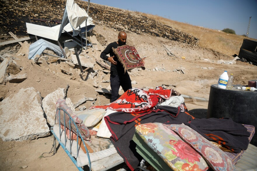 A Palestinian man collects his belongings after his structure was demolished by Israeli forces in Jordan Valley in the Israeli-occupied West Bank October 19, 2020. Palestinian groups say another settlement was destroyed in the same area on Tuesday.