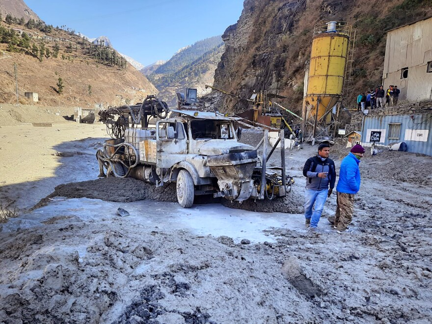 People inspect the site near a damaged hydropower project at Reni village in the Chamoli district in northern India after a portion of the Nanda Devi glacier broke off on Sunday.