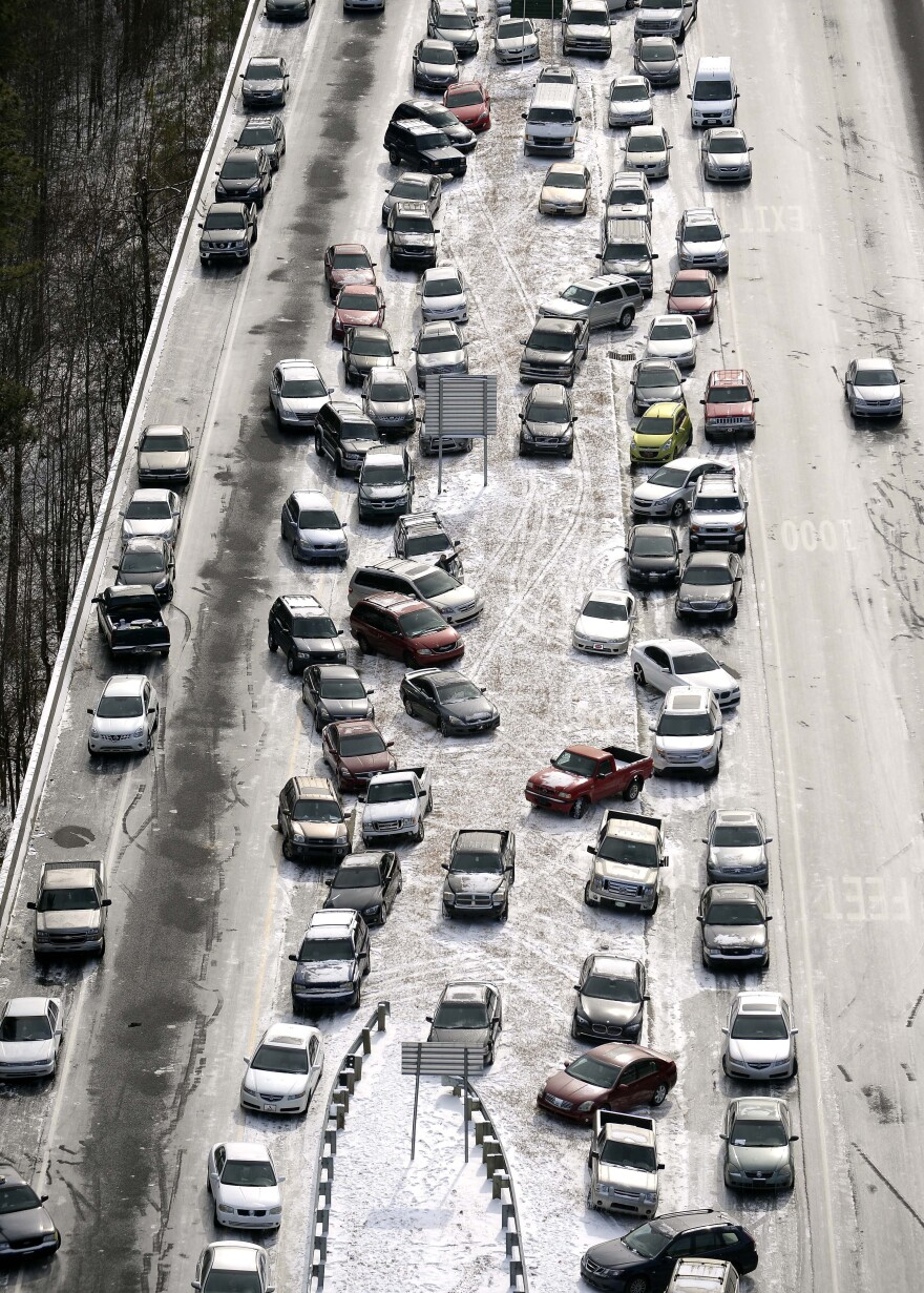 Abandoned cars sit on Interstate 75 in Atlanta. Traffic halted Tuesday during an ice and snow storm. Two days later, drivers can start retrieving their vehicles.