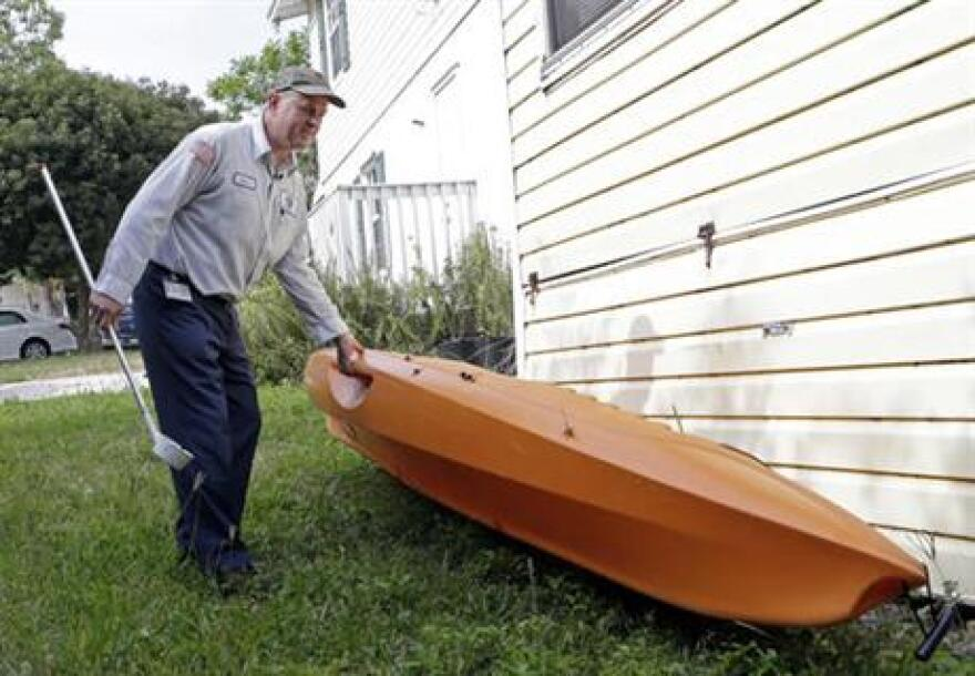 In this photo taken Thursday, May 12, 2016, Steve Noe, Martin County mosquito specialist, turns over a kayak looking for standing water where mosquitos breed during an inspection outside a home, in Rio, Fla.