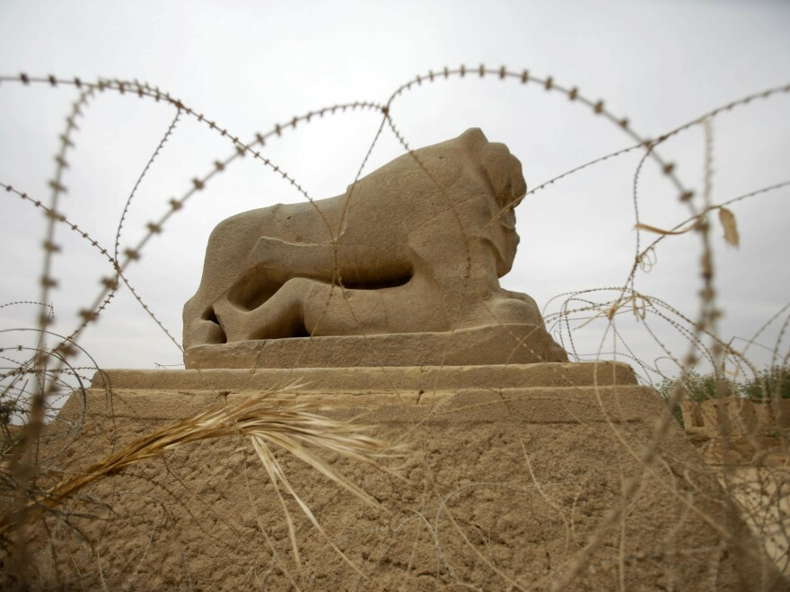 Barbed wire surrounds the Lion of Babylon, seen in 2012 at the archaeological site of Babylon.
