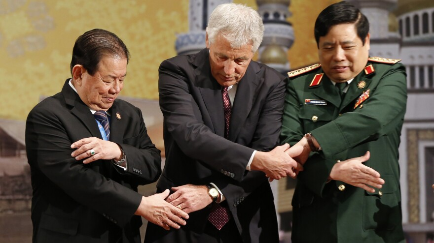"U.S. Defense Secretary Chuck Hagel, center, chains his hands with his counterparts from Vietnam, right, and Thailand before the ASEAN meeting in Bandar Seri Begawan, Brunei, on Thursday. The trip's message: The U.S. is committed to its ""rebalance"" toward the Asia-Pacific region."