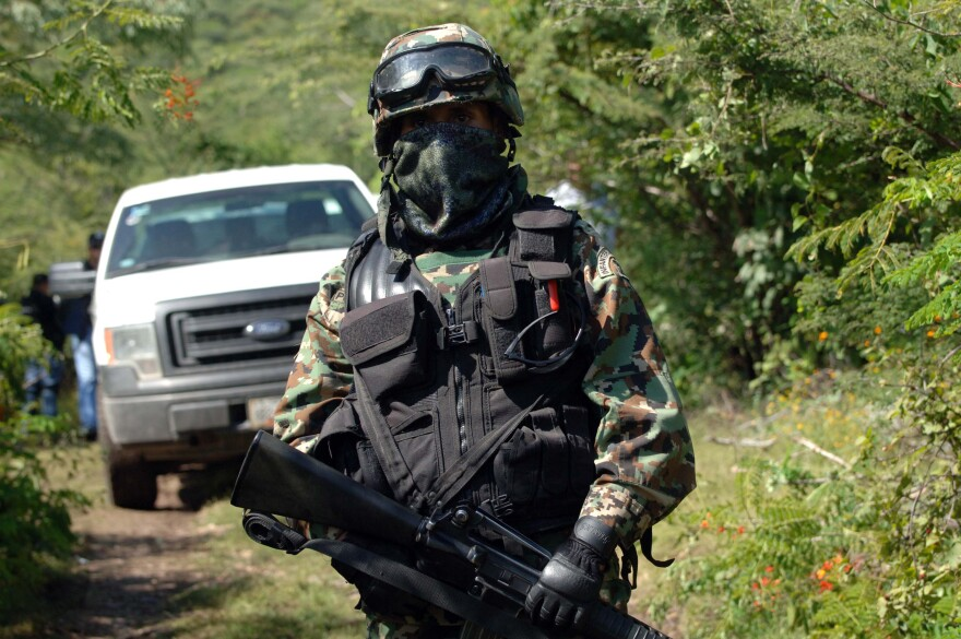 A Mexican navy marine guards the road that leads to the site where an alleged clandestine mass graves were found near the city of Iguala, Mexico.