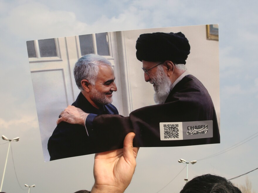 A protester on Friday raises an undated image of Iranian Supreme Leader Ayatollah Ali Khamenei (right) meeting with Iranian Maj. Gen. Qassem Soleimani.