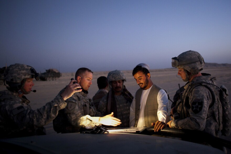 During a patrol in 2009, Gen. Abdul Raziq of Afghanistan's border police (center) talks with U.S. Lt. Col. William Clark near the Afghan border with Pakistan.