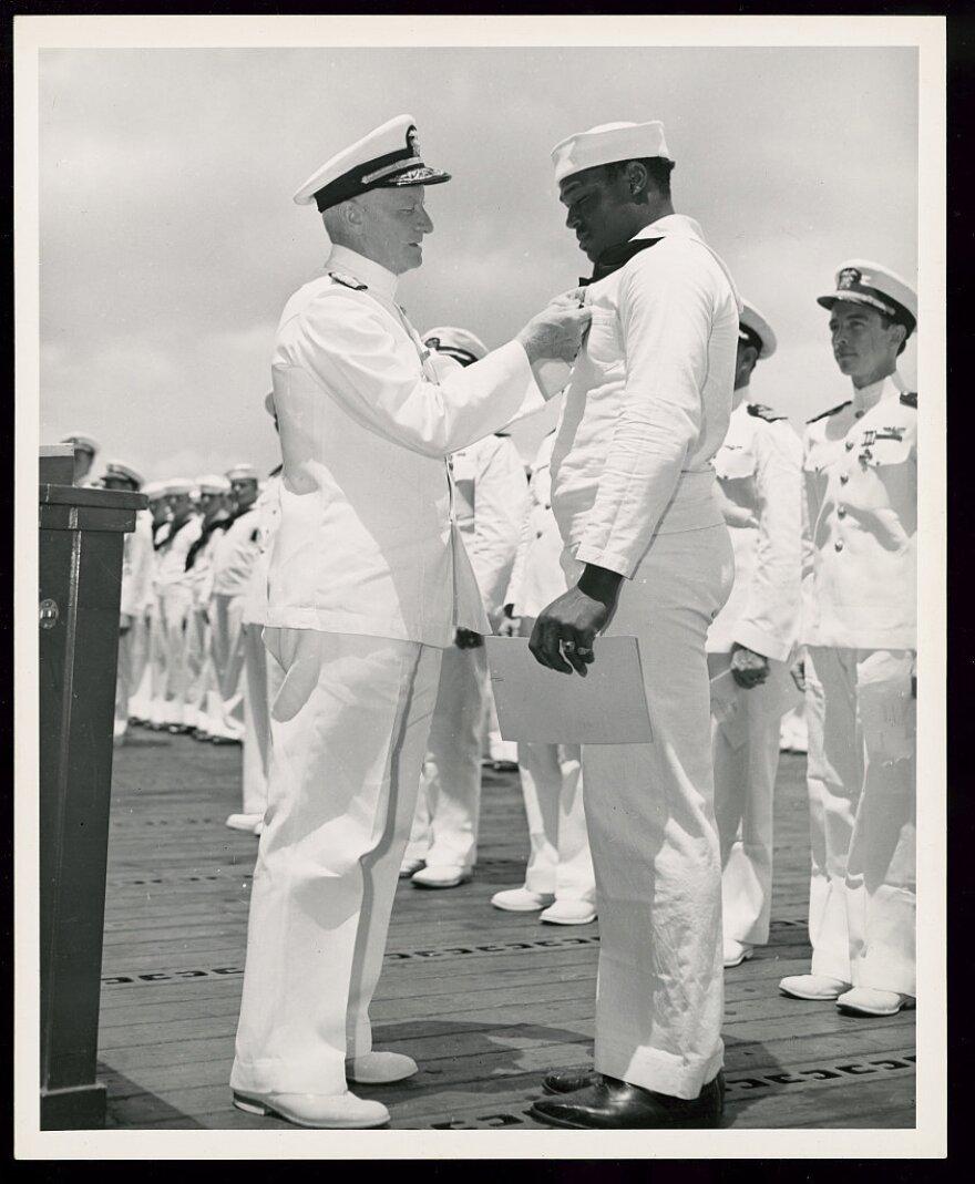 Adm. Chester W. Nimitz, commander in chief of the U.S. Pacific Fleet, pins the Navy Cross on Doris Miller