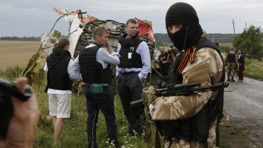 With pro-Russian separatists standing guard, investigators from the OSCE arrive at the crash site of the Malaysia Airline jet near the village of Hrabove in Eastern Ukraine on Friday.
