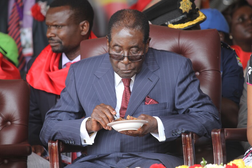 Zimbabwean President Robert Mugabe eats his cake during Saturday's celebrations to mark his 92nd birthday. Mugabe appears to have no plans to step down as feuding over his successors threatens to tear Zimbabwe's ruling party apart.