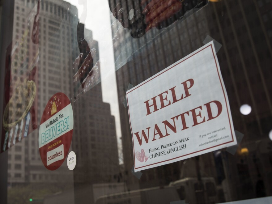 """A """"help wanted"""" sign hangs on a window of a restaurant in New York City. The U.S. economy gained a stronger-than-expected 223,000 jobs last month and the unemployment rate edged down to an 18-year low."""