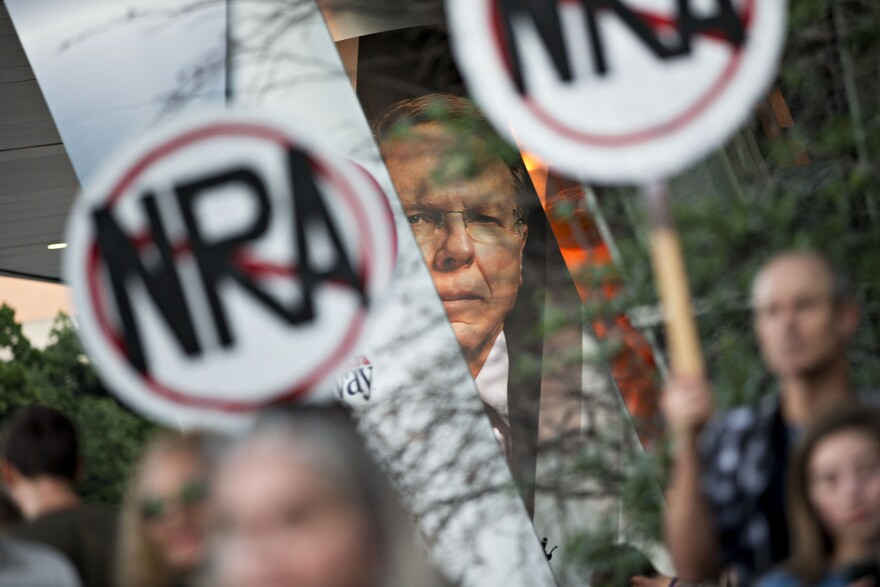 "Protesters gather beneath a banner featuring Wayne LaPierre, CEO of the National Rifle Association, during a rally outside the NRA's annual meeting in Dallas in May. When the NRA told doctors to ""stay in their lane"" instead of weighing in on gun policies, Dr. Joseph Sakran used Twitter to express his outrage."