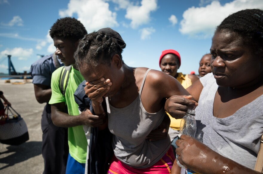 Nicole Guillaume, who was nursing her 2-year-old son while waiting with several hundred other Haitians and Bahamanians at the port of Marsh Harbour, fainted in the heat.