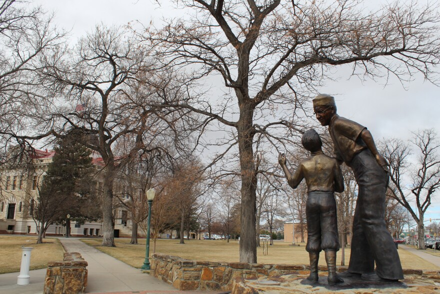 A statue of a man offering food to a little boy with the Logan County courthouse in the background.
