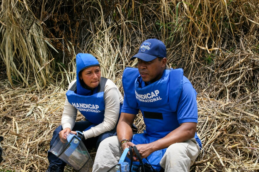 Johanna Galuis (left) and Aderito Ismael take a break while de-mining a field in the Cauca region of Colombia.