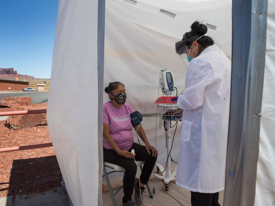 A nurse checks vitals for a Navajo woman, who came to a coronavirus testing center in Arizona, complaining of virus symptoms.
