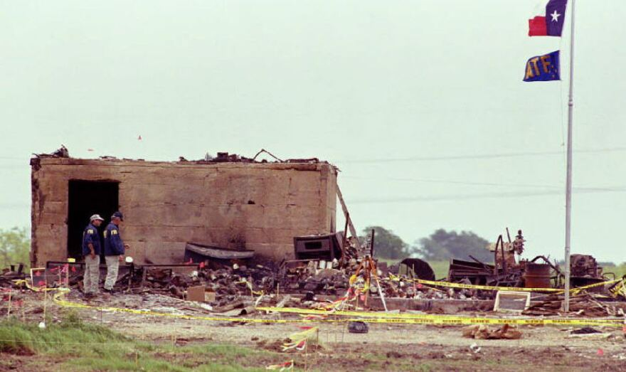 The Texas and Bureau of Alcohol, Tobacco and Firearms flags fly at half-staff over the only structure left standing after a fire destroyed the Branch Davidian compound on April 19, 1993, in Waco, Texas. The blaze ended a 51-day standoff between federal agents and the cult lead by David Koresh.