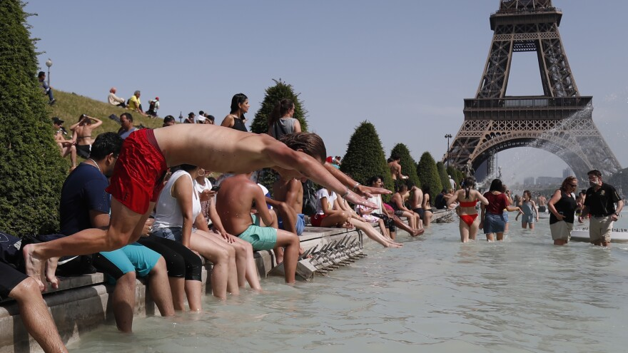 A boy jumps into the water of the Trocadero Fountain in Paris on Friday, to find relief from the heat wave.