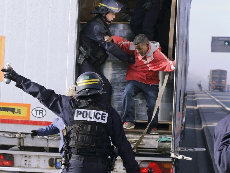 French riot policemen force out migrants who were hidden in a truck that was making its way to the ferry terminal in Calais in western France on Wednesday. The cross-Channel port has become the last barrier for economic and political migrants trying to enter Britain illegally.