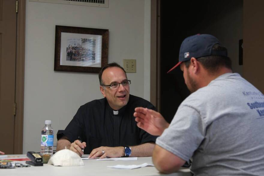 Father Jim Sichko, a Catholic priest and motivational speaker based in Lexington, paid the electric bills of about 200 out-of-work coal miners in Harlan on Monday.