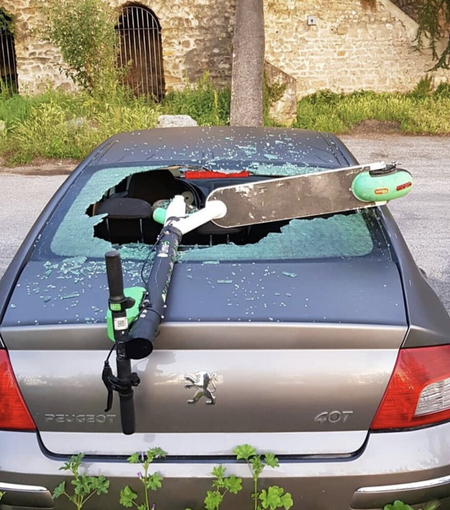 E-scooter resting on a car that has a broken windshield. Courtesy: @birdgraveyard
