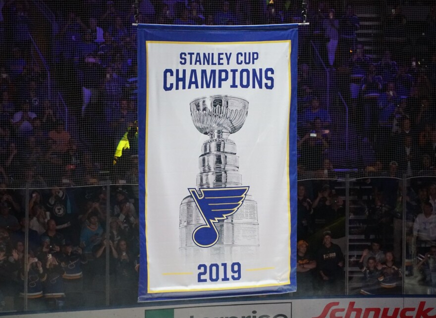 Fans watch as the Stanley Cup championship banner is raised to the rafters at Enterprise Center.